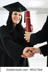 Young female graduating and receiving diploma at university