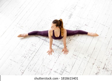 Young female gymnast doing a frontal split pose in a top down view on a white floor in a high key gym in a health and fitness concept with copyspace