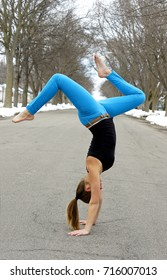 young female gymnast doing handstand in city street. snow cover and trees. she is wearing bright royal blue pants and black top. long pony tail touching the ground.