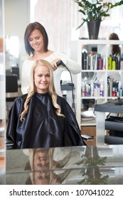 Young Female in hair salon having her hair styled