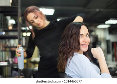 Young female hairdresser fixing hair of gorgeous smiling woman with hairspray