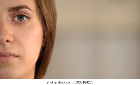 Young female half face looking into camera, average woman opinion statistics