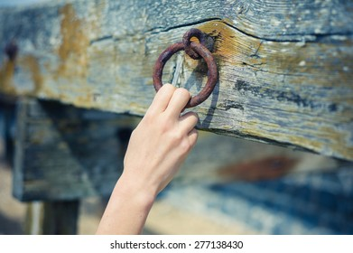 A young female hand is grabbing an old rusty chain attached to a wooden beam