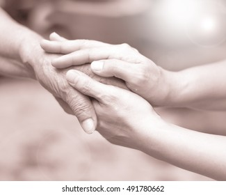Young female hand holding old hand to comfort her in black and white color with lens flair effect.National Family Caregivers, National Hospice and Home Care Month in November.World Disability Day