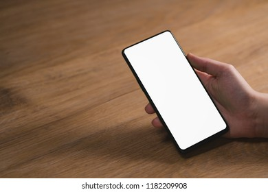 young female hand holding smartphone with big screen on wood oak table with copy space