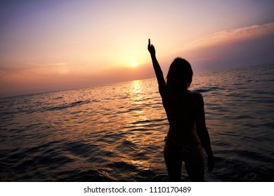 Young Female hand shows the sign of Fuck you in the summer sunset.  Young woman is showing fuck off with the middle finger