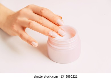 Young female hand using moisturizing cream from jar, concept of beauty and skincare.
