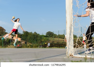 Young female handball player trying to give a goal during a game.