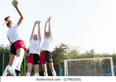 Young female handball players trying to defent goal during a game. Space for text.