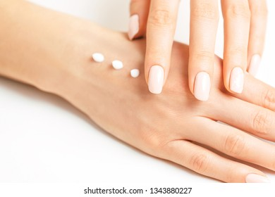 Young female hands applying moisturizing cream for smooth skin, concept of skincare and beauty.