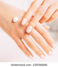 Young female hands with manicure of beige natural color applying moisturizing cream, concept of skincare and beauty.
