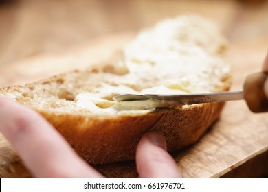 young female hands spreading butter on bread, closeup shot