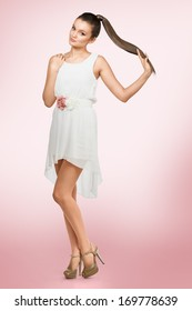 Young female with healthy shining brown hairs put in pony tail. White dress.