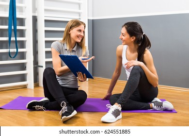 Young female and her fitness instructor are having conversation at the gym about exercising.Woman and personal trainer talking