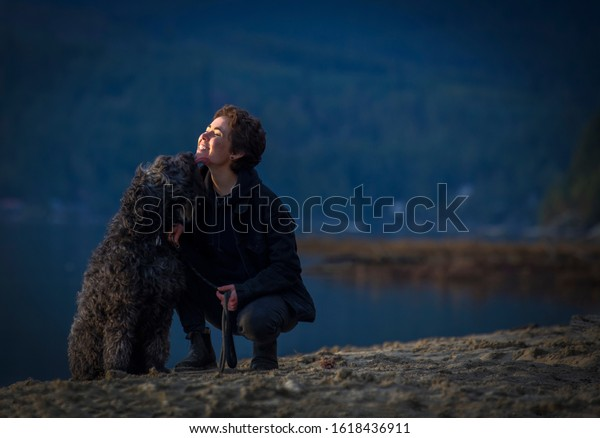 Young female with her pet dog licking her face by the lake.