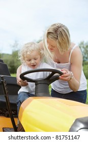 Young female with her son holding steering wheel