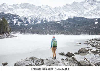 Young female hiker with backpack enjoying view to frozen lake Eibsee, winter Bavarian forest and snowy mountains at base of Zugspitze, Alps - nature lovers travel concept
