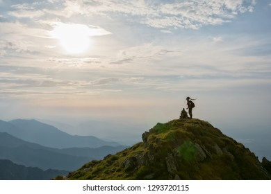 Young female hiker celebrating success on the top of the mountai