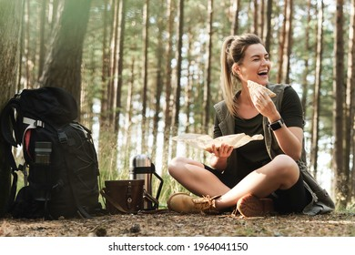 Young female hiker during small halt eating sandwich in green forest - Shutterstock ID 1964041150