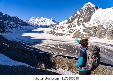 Young female hiker looking at Glacier de Corbassiere. Hiking a mountain trail around Glacier and Grand Combin in Valais Alps (Pennine Alps), Switzerland.