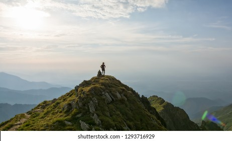 Young female hiker looking over the valley from the top of the mountain