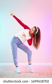 Young female hip-hop dancer against color wall