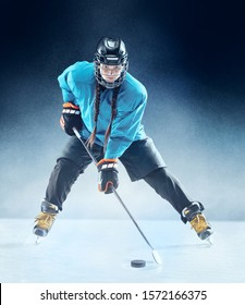 Young female hockey player with the stick on ice court and blue background. Sportswoman wearing equipment and helmet practicing. Concept of sport, healthy lifestyle, motion, movement, action.