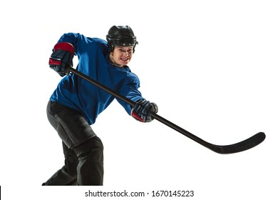 Young female hockey player with the stick on ice court and white background. Sportswoman wearing equipment and helmet training. Concept of sport, healthy lifestyle, motion, action, human emotions.