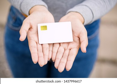 Young female holding blank credit card, outdoor