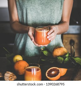 Young female holding glass of freshly squeezed blood orange juice or smoothie in hands near concrete kitchen counter, square crop. Healthy lifestyle, vegetarian, alkaline diet, spring detox concept