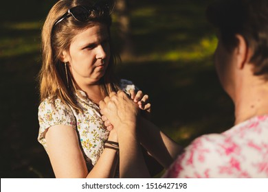 Young female holding senior's hand for support outdoors - Casually dressed girl offering help to elderly woman in the park - Pretty emphatic lady with brown hair showing affection to an older person