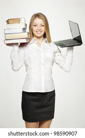 Young female holding heavy stack of books in one hand and laptop in another, isolated on gray background