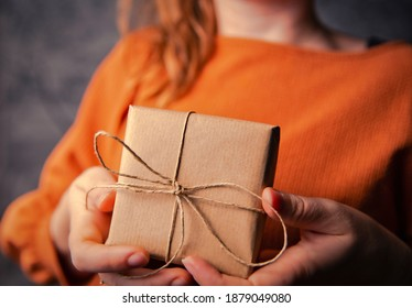 Young Female holding a kraft gift box, wrapped in plain brown paper, Valentines day, Birthday, Mothers Day present or gift concept selective focus, dark background closeup