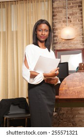 young female holding papers in the office