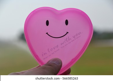 Young female holding smile pink plastic heart on sky.Valentine's Day.