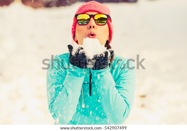 Young female holding snow. Relax fun in winter park. Health nature fashion fitness concept.