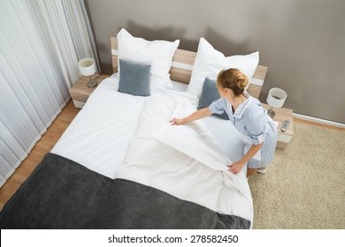 Young Female Housekeeper Changing Bedding In Hotel Room