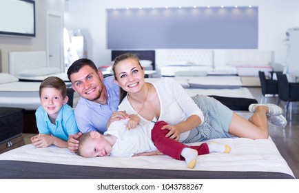 Young female with husband and children are choosing comfortable mattress in home furnishings store.
