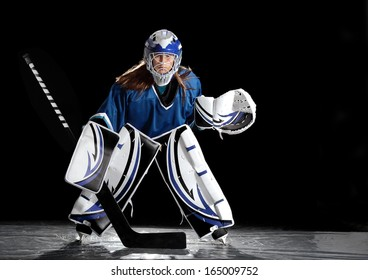 Young female ice hockey goalie in blue jersey.