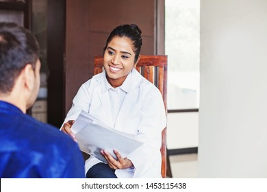 Young female Indian doctor consulting a patient while holding medical reports in her hands