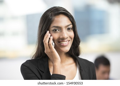 Young female Indian office executive using a smart phone