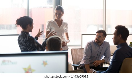 Young female indian team leader coach mentor explain strategy to colleagues at diverse corporate group meeting in office room, multiethnic staff talking at work break discussing new business plan