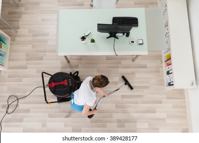 Young Female Janitor Cleaning Wooden Floor With Vacuum Cleaner