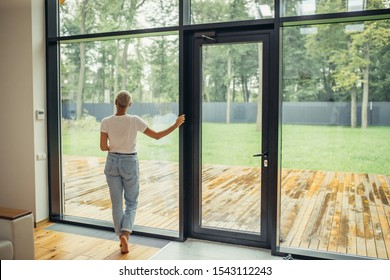 Young female in jeans stand looking at panoramic window. Morning, dreamtime, relaxing