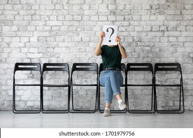 Young female job applicant sit on chair in corridor hide face hold sheet paper with question mark, millennial woman work candidate wait for interview or recruitment talk, hiring, employment concept