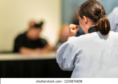Young Female Karate Girl Stands in Fighting Stance with Hands Up - Shallow Depth of Field