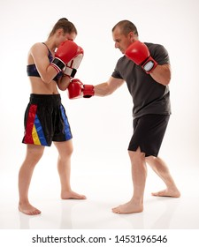 Young female kickboxer sparring with her coach on white background