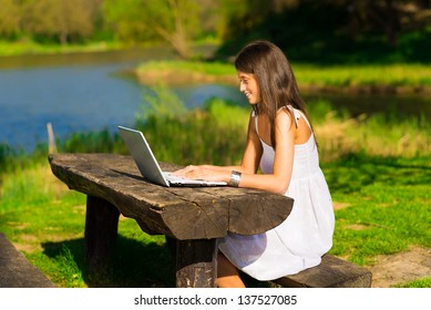 Young female with a laptop sitting a beautiful lake