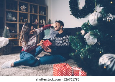 Young female laughing and closing eyes to boyfriend while giving him present.