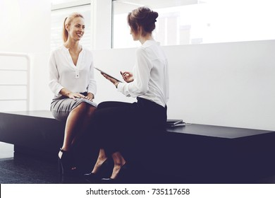 Young female lawyer is holding touch pad and talking something to her smiling client, while they are sitting in modern office interior. Smart woman using digital tablet for consultation with customer